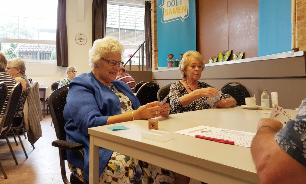 Mevrouw Van Laarhoven en mevrouw De Beer aan het kaarten in Ons Honk.